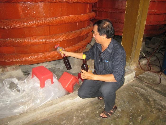 Chủ nhà đang chiết nước mắm vào chai
